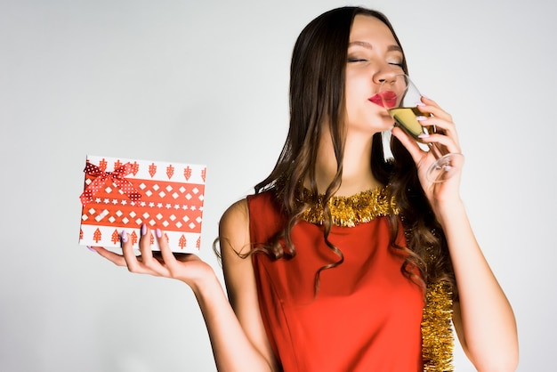 Happy beautiful girl in red dress celebrates the new year 2018, drinks champagne, holds a gift
