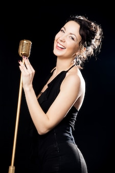 Happy beautiful girl singer laughing behind retro microphone