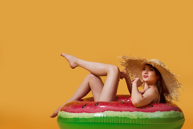 Happy beautiful girl in a summer straw hat sitting on an inflatable ring resting isolated on a yello...