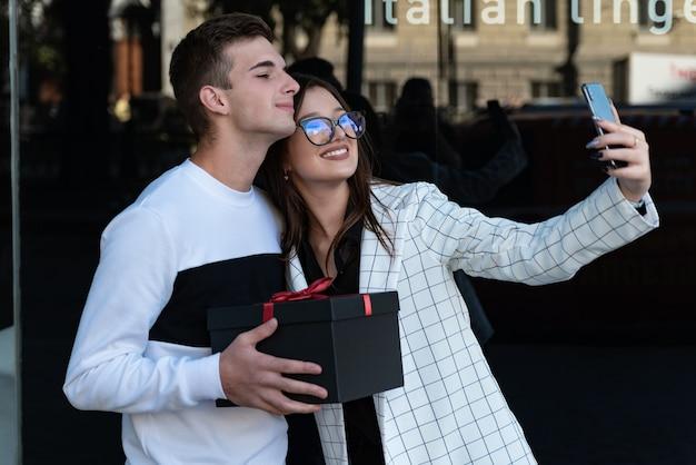 행복한 아름다운 소녀는 남자친구와 셀카를 찍는다. 남자는 여자에게 선물을 줍니다. 도시에서 데이트에 행복 한 커플입니다.