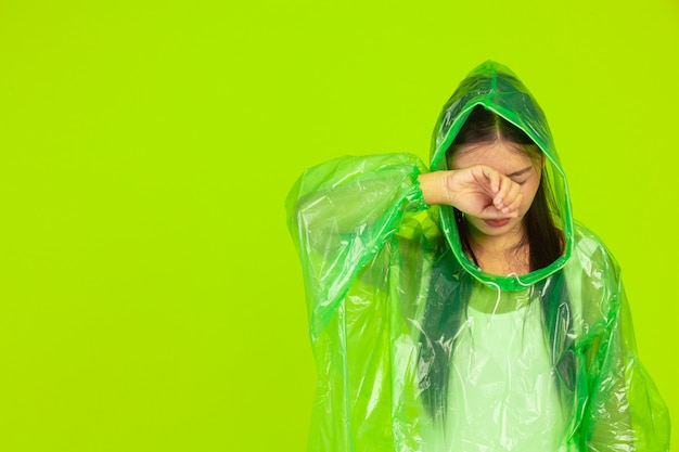 Happy beautiful girl, wearing green clothes, umbrella and coat, rainy day.