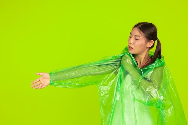 Happy beautiful girl, wearing green clothes, umbrella and coat, rainy day.
