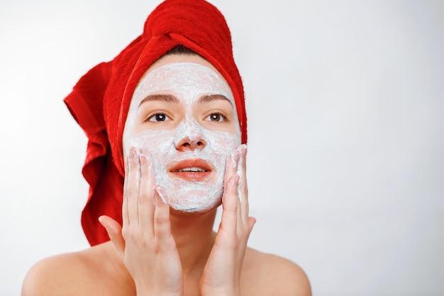 Счастливая красивая девушка с красным полотенцем на голове наносит скраб на лицо большого портрета на белом фоне
