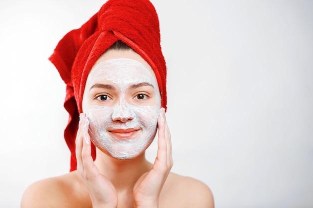 Счастливая красивая девушка с красным полотенцем на голове наносит скраб на лицо