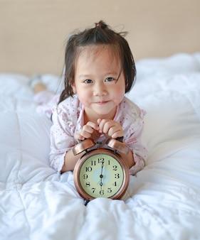 ベッドに目覚まし時計を持つ、美しい美しい女の子