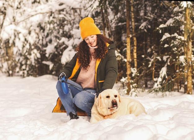 자연 속에서 겨울에 그녀의 흰 강아지 래브라도와 함께 행복 한 아름 다운 소녀