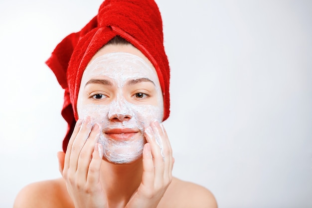 Happy beautiful girl with a red towel on her head applies a scrub on the face of a large portrait on a white background