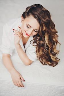 Счастливый красивая девушка с блестящими брюнетка волосы и макияж, улыбаясь вниз.