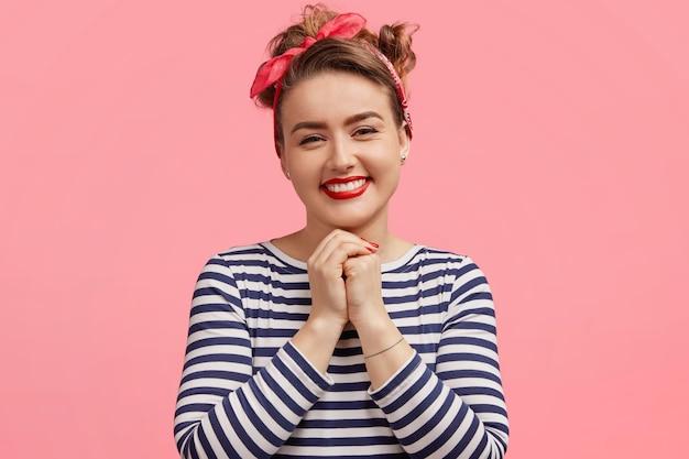 Felice bellissima bellissima modella europea in maglione a righe casual, tiene le mani unite, si compiace di ricevere complimenti, esprime emozioni positive sincere, modella da sola al coperto.