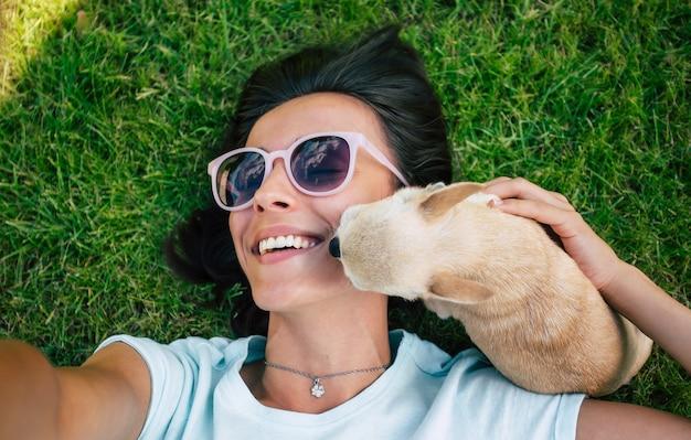 サングラスをかけた幸せな美しいヒップスターの女性は、彼女が芝生に横たわって、彼女の小さなかわいい犬と一緒に自分撮りをしている間楽しんでいます