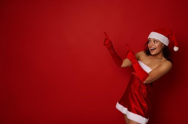 산타 카니발 의상을 입은 행복한 아름다운 히스패닉 여성은 빨간색 배경에 크리스마스와 새해 광고를 위한 복사 공간에 이빨 미소 포인트와 함께 미소