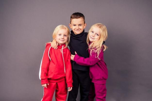 스포티한 운동복을 입은 행복한 아름다운 아이들. 어린 소년과 검은 배경의 스튜디오에서 껴안고 있는 두 명의 귀여운 소녀. 힙합 댄서들은 세련된 면 스포츠 정장 잠옷 후드 패션 모델 어린이를 입습니다.
