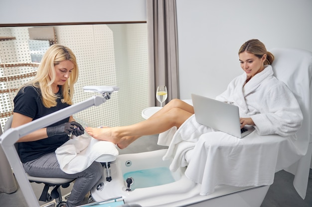 Счастливая красивая леди серфинг в интернете на ноутбуке, пока маникюрный мастер делает для нее педикюр