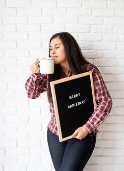 メリークリスマスという言葉で黒い文字板を持つ幸せな美しいラテン女性