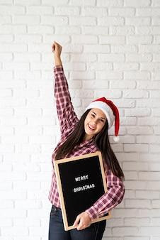 メリークリスマスという言葉で文字板と幸せな美しいラテン女性