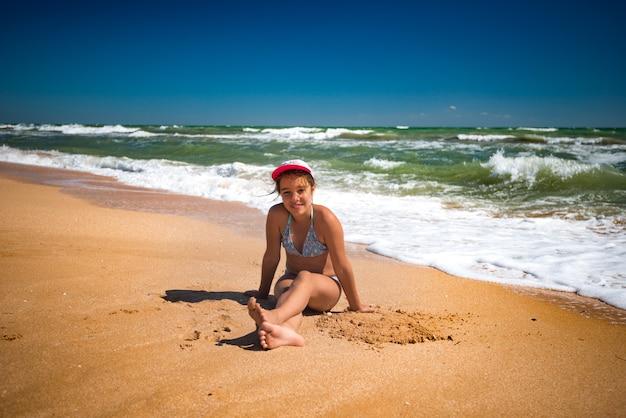 행복 한 아름 다운 작은 소녀 해변에서 쉬고 햇살 따뜻한 여름날에 모래를 가지고 노는