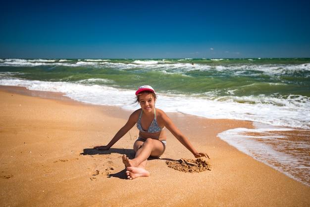 ビーチで休んで、晴れた暖かい夏の日に砂で遊ぶ幸せな美しい少女