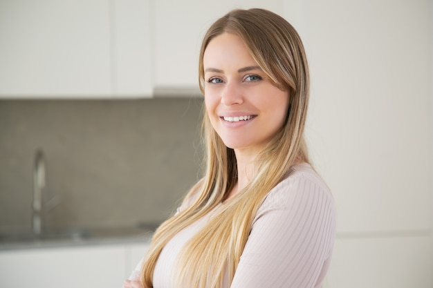幸せな美しい長い髪の若い女性がキッチンでポーズ