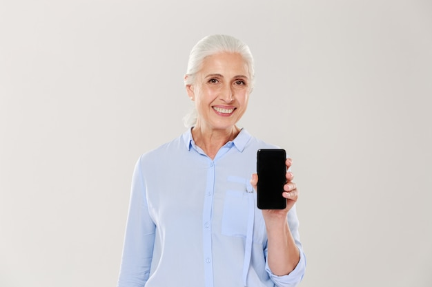 Happy beautiful mature woman showing smartphone with blank black screen isolated
