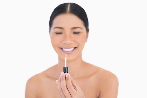 Счастливая красивая модель с блеском для губ перед ней