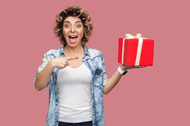 곱슬머리 헤어스타일을 한 파란 셔츠를 입은 아름다운 현대 젊은 여성이 입을 벌리고 큰 선물 상자를 들고 손가락을 가리키며 카메라를 바라보고 있습니다. 스튜디오 촬영, 분홍색 배경