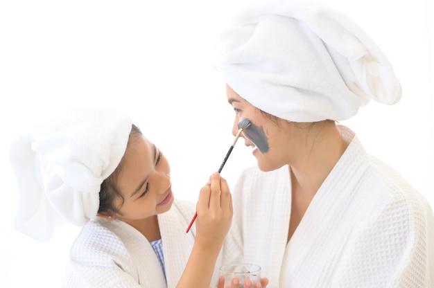 寝室、家族と美容の概念でフェイスマスクを適用する白いバスローブで幸せな美しいママと娘