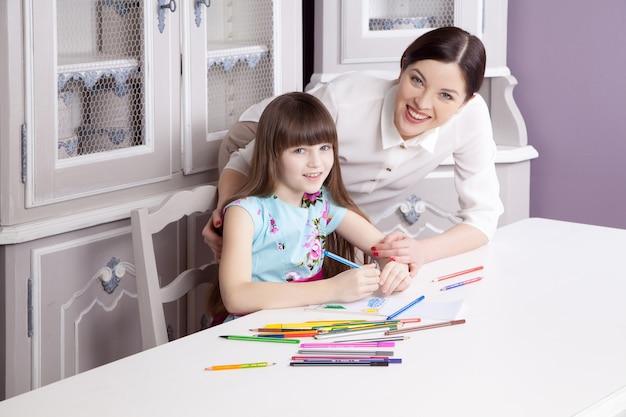 Счастливая красивая мать учит свою дочь рисовать, рисовать и улыбаться и смотреть в камеру. студийный снимок.