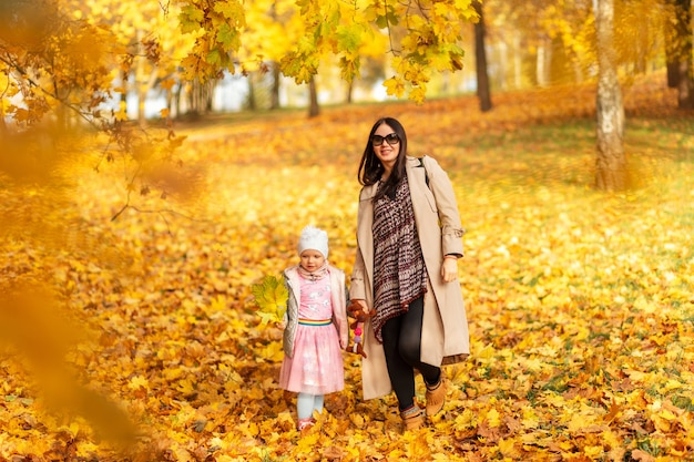Happy beautiful mother woman with her daughter child in fashionable clothes are walking in the autumn park with yellow foliage outdoors