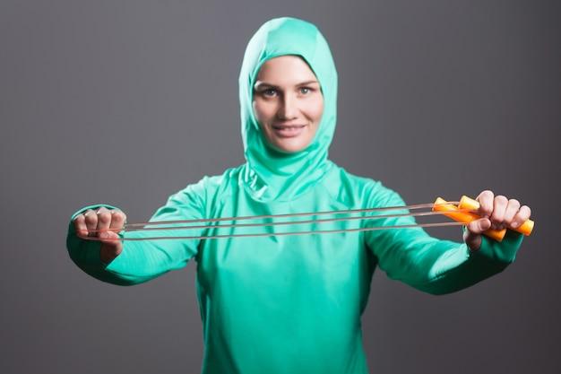 녹색 히잡이나 이슬람 스포츠를 입은 행복한 아름다운 이슬람 여성은 서서 줄넘기를 들고 보여주고 이빨 미소로 카메라를 바라보고 있습니다. 어두운 회색 배경에 고립 된 실내 스튜디오 촬영.