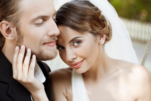 Счастливые красивые молодожены в костюме и свадебное платье, улыбаясь, наслаждаясь.