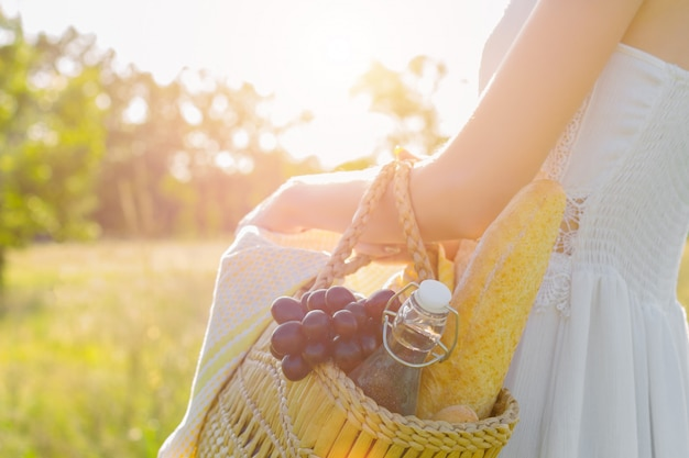 Happy beautiful positive fun smiling girl woman wear straw hat long white dress on big large wide summer hot spring sunny green light field between fruit trees and have a picnic with fruits, baguette