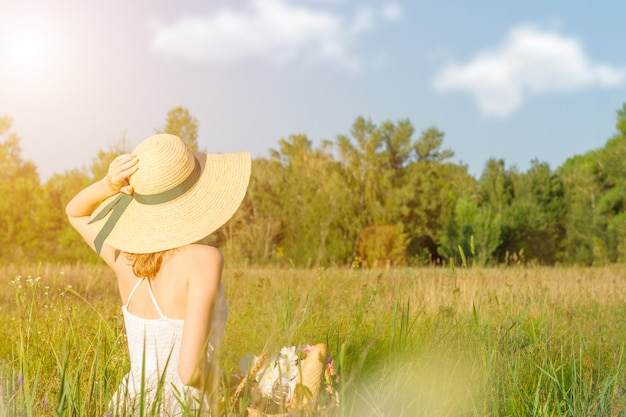 Happy beautiful positive fun smiling girl woman wear straw hat long white dress sit on big large wide summer hot spring sunny green sunray light field between fruit trees and have a picnic with fruits