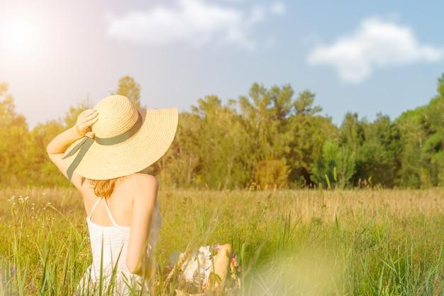 幸せな美しい肯定的な楽しい笑顔の女の子女性麦わら帽子の長い白いドレスを着て大きな大きな広い夏の温泉に座って果物の木の間の日当たりの良い緑の太陽光線ライトフィールドと果物のピクニック