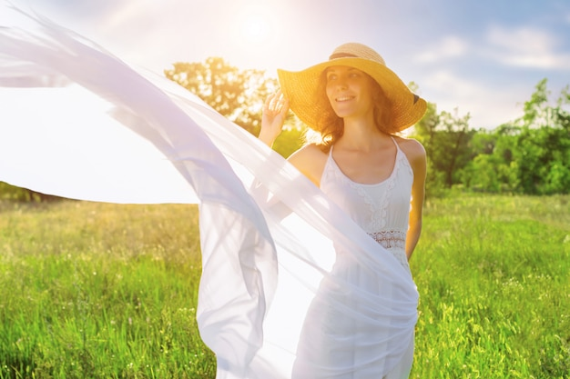 Happy beautiful positive fun smiling girl woman wear straw hat strong wind air waves long white dress shawl chiffon fabric on big large wide summer hot spring sunny green sunray light field blue sky
