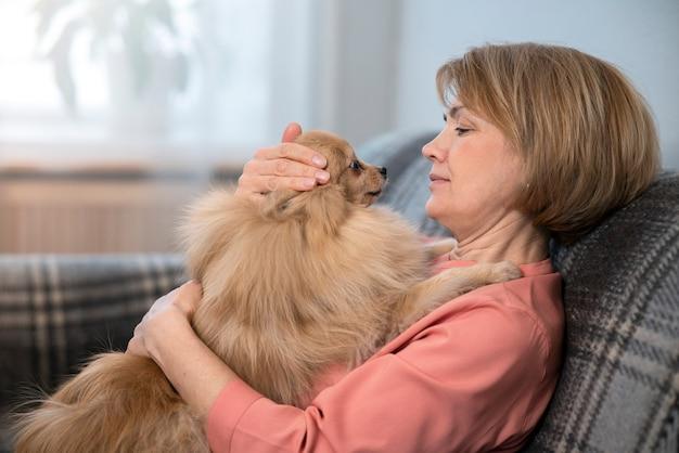 Счастливая красивая позитивная дама, пожилая старшая женщина сидит на диване у себя дома со своим питомцем, обнимая