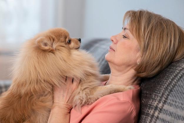 Счастливая красивая позитивная дама, пожилая старшая женщина, сидящая на диване в гостиной дома с ней
