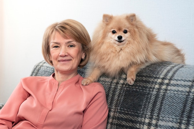 Happy beautiful positive lady, elderly senior woman sitting at couch in living room at home with her pet, pomeranian spitz dog, small puppy and smiling. people care, love animals