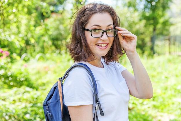 녹색 공원 배경에 웃는 배낭과 안경에 행복 한 아름 다운 긍정적인 학생 소녀. 점심 시간 동안 캠퍼스에서 휴식을 취하는 여자. 교육 및 레저 개념입니다.