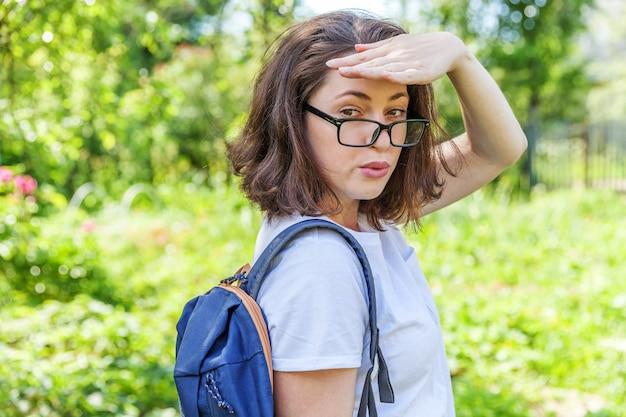 배낭 녹색 공원 배경에 웃 고 안경에 행복 한 아름 다운 긍정적 인 학생 소녀.