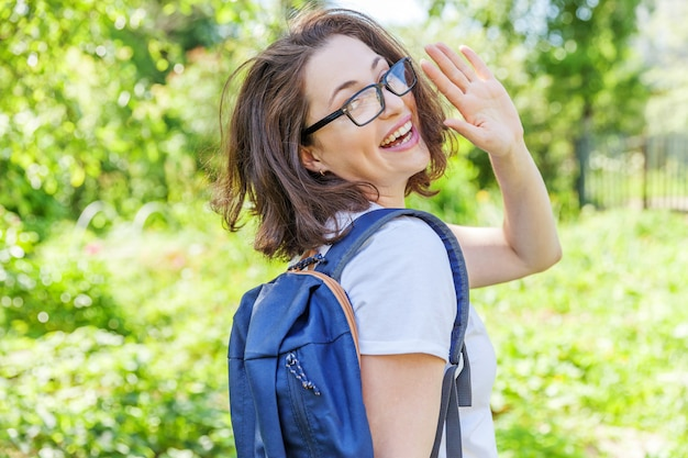 緑豊かな公園の壁に笑みを浮かべてバックパックと眼鏡で幸せな美しい肯定的な学生の女の子。昼休み中にキャンパスで休憩を持つ女性。教育とレジャーの概念。