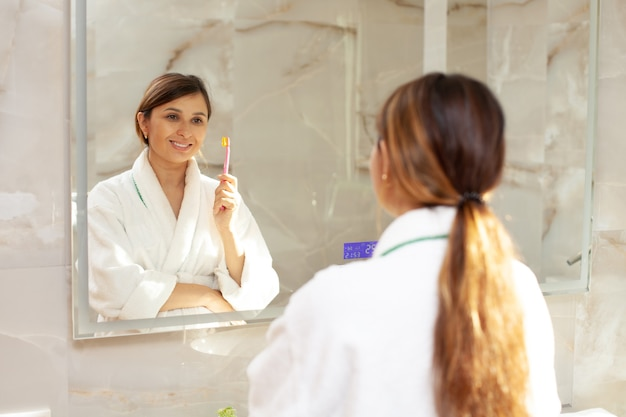 A happy beautiful pregnant woman in a bathrobe brushes her teeth. reflection in the mirror. beautiful interior. morning and evening routine. health care. dental care. high quality photo