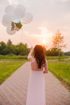 Happy beautiful pregnant woman in pink long dress walking with air balloons in the green p