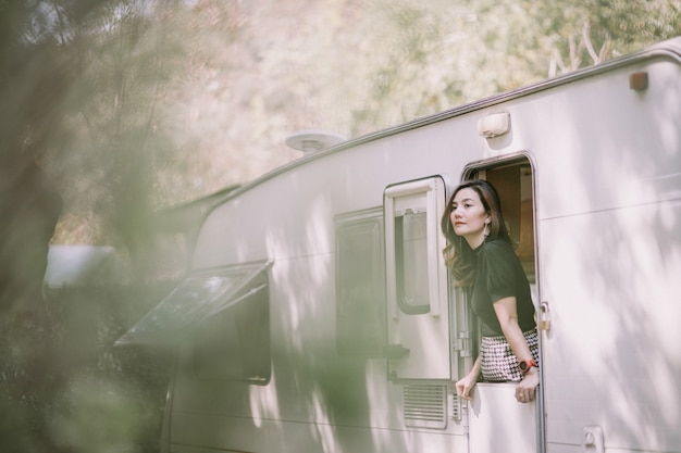 Счастливая красивая довольно азиатская женщина у окна автодома