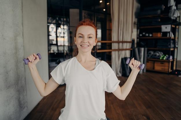 흰색 티셔츠를 입은 행복한 아름다운 빨간 머리 여성은 두 손에 아령을 들고 체육관에서 일상적인 필라테스 운동을 하고, 핏볼에 앉아 카메라를 보며 웃고 있습니다. 피트니스 및 건강한 라이프 스타일 개념