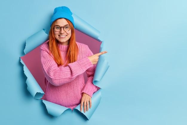 Felice bella giovane donna rossa punta a destra allo spazio della copia, indossa un cappello blu e un maglione blu lavorato a maglia