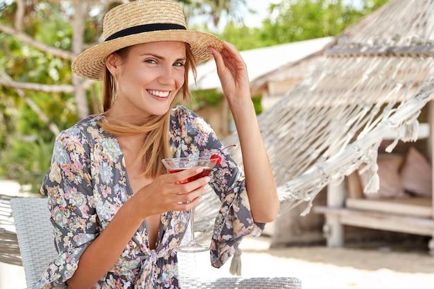 Felice bella donna rilassata si diverte all'aperto, indossa cappello e camicia di paglia, beve cocktail freschi, si siede su una sedia vicino all'amaca, ricrea in un paese tropicale. la donna allegra ha festa in spiaggia