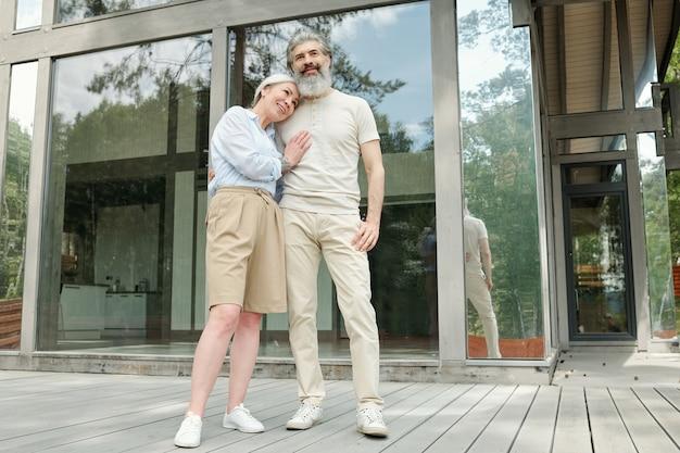 カントリーハウスに立ち向かいながらお互いを見つめる夏の衣装で幸せな美しい年配のカップル