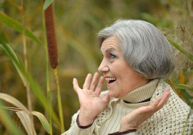 秋の公園で幸せな美しい年配の女性