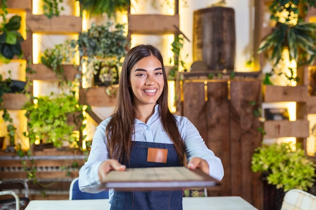 Happy beautiful smiling waitress wearing apron giving a folder menu in a restaurant, looking at camera, standing in cozy coffeehouse, good service
