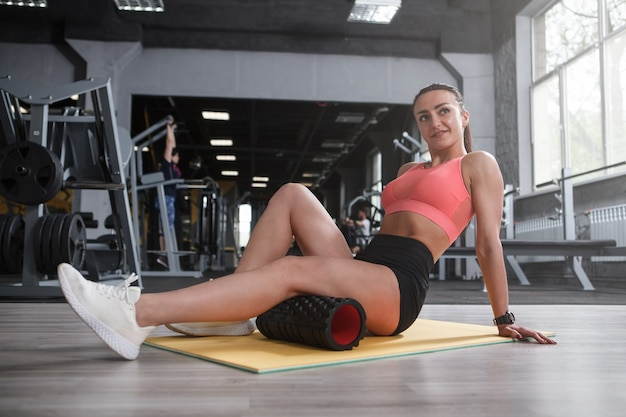 Happy beautiful sportswoman relaxing hamstrings on foam roller after working out